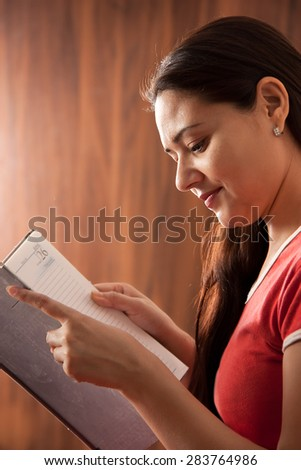 Close up portrait of a beautiful smiling young Indian woman in red dress reading her diary over dark background