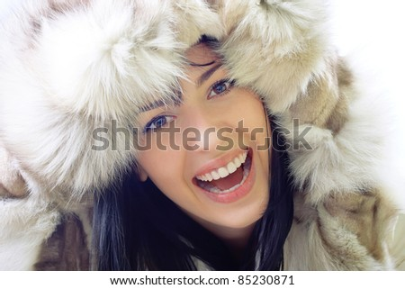 close-up portrait of a beautiful smiling young woman wearing fur