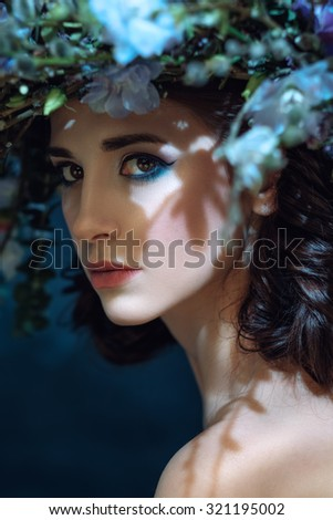 Close-up Portrait of a beautiful spring girl with wreath on head. Shallow depth of field. Focused on eyes.