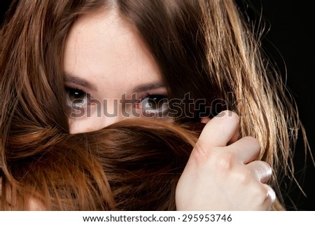 Close-up portrait of a beautiful woman covers the face by long brown hairs - stock photo