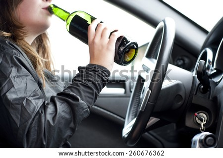 Close up portrait of a beautiful woman drinking alcohol while driving a car, do not drink and drive concept - stock photo