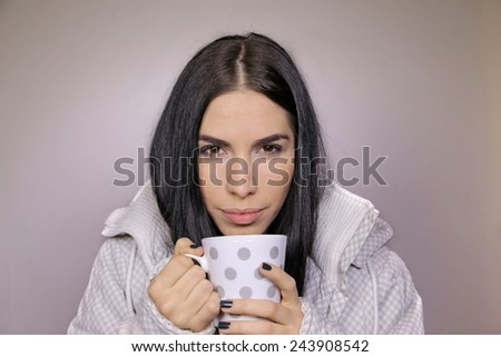 Close up portrait of a beautiful woman holding and drinking a hot and comforting cup of tea or coffee beverage, warming up in the cold winter  - stock photo