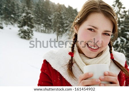 Close up portrait of a beautiful woman in the snow mountains, celebrating christmas and holding a hot cup of tea or coffee beverage keeping warm during a cold winter day, smiling outdoors. - stock photo