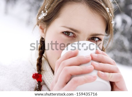 Close up portrait of a beautiful woman in the snow mountains, holding and drinking a hot and comforting cup of tea or coffee beverage, warming up in the cold winter outdoors. - stock photo