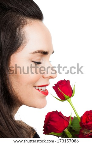 Close-up portrait of a beautiful woman smiling and smelling a rose. Isolated on white. - stock photo
