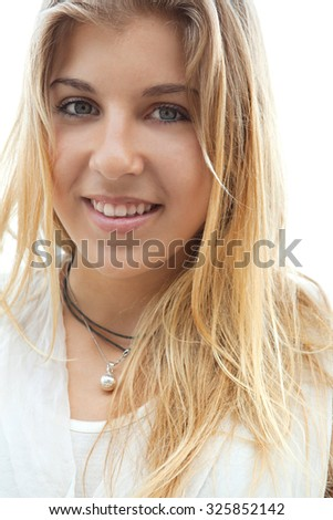 Close up portrait of a beautiful young adolescent blond girl with blue eyes and friendly expression, smiling looking at camera on vacation summer holiday. Healthy and well being lifestyle, outdoors.