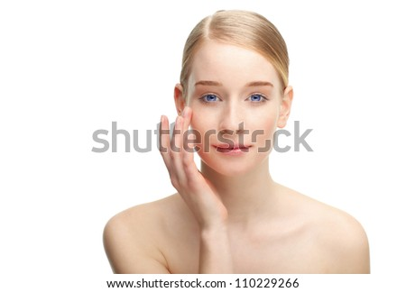 Close up portrait of a beautiful young blond woman, touching her face with her hand, against white background.