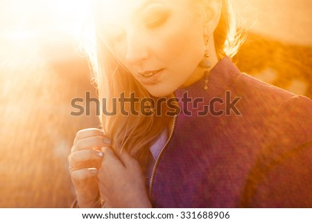 close-up portrait of a beautiful young blonde girl in stylish  autumn with dark red full lips smiling at sunset on a sunny day and posing lifestyle in the city - stock photo