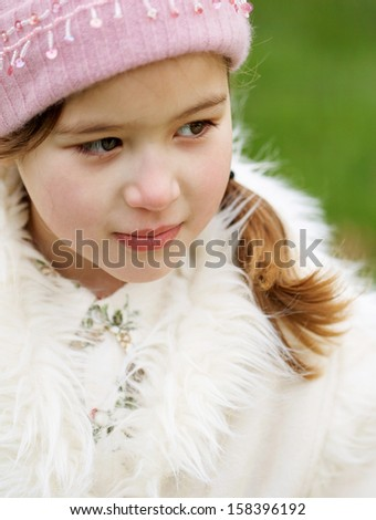 Close up portrait of a beautiful young child girl standing in a green park looking away and being thoughtful during a cold winter day, wearing a warm coat and a pink hat, outdoors. - stock photo