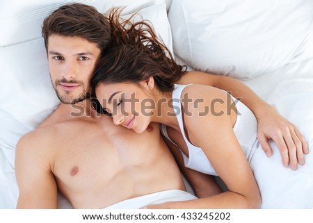 Close-up portrait of a beautiful young couple lying in bed at home - stock photo