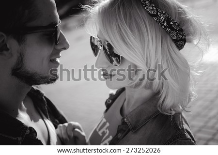 close-up portrait of a beautiful young couple on a sunny day, hipsters, girl blonde with red lips and wearing sunglasses and attractive guy with a beard - stock photo