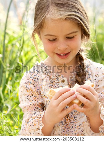 Close up portrait of a beautiful young girl sitting in a long green grass field enjoying and eating a fresh sandwich during a summer holiday. Food and outdoors lifestyle in nature. - stock photo
