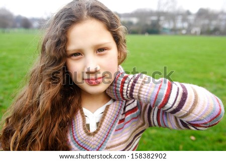 Close up portrait of a beautiful young girl with a gentle smiling expression, wearing a red knitted stripy jumper while in a green grass field park during winter autumn day outdoors. - stock photo
