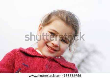 Close up portrait of a beautiful young girl with a gentle smiling expression, wearing a red knitted jumper against the sky while in a park during winter autumn day outdoors. - stock photo