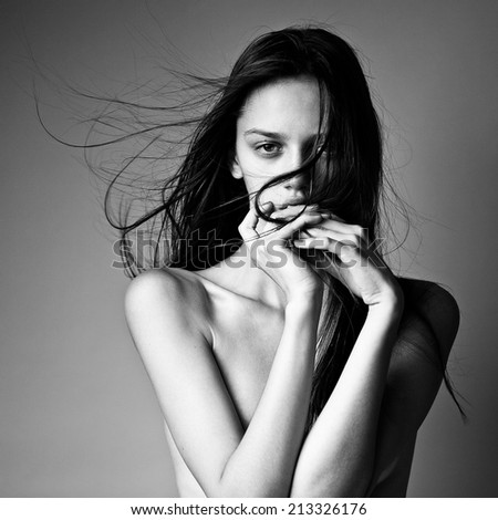 close-up portrait of a beautiful young girl with long hair flying in the wind. black and white image - stock photo