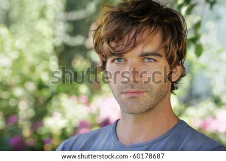 Close-up portrait of a beautiful young man against blurred garden background with lots of copy space - stock photo