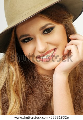 close up portrait of a beautiful Young smiling blond lady wearing beige trilby hat and leaning on her hand