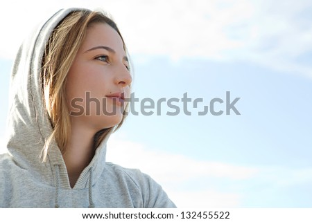 Close up portrait of a beautiful young sports woman wearing a hood during a sunny morning against a blue sky. - stock photo