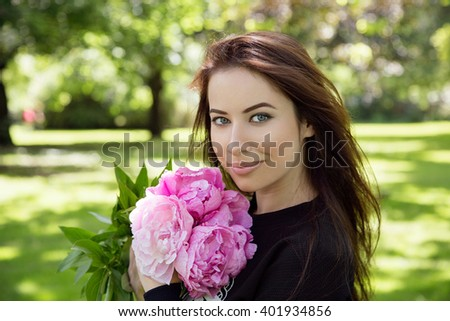 Close up portrait of a beautiful young woman (Caucasian, brunette / redhead, sparking blue eyes, cat eye makeup, luscious lips) holding a bouquet, looking happy, excited; park - stock photo