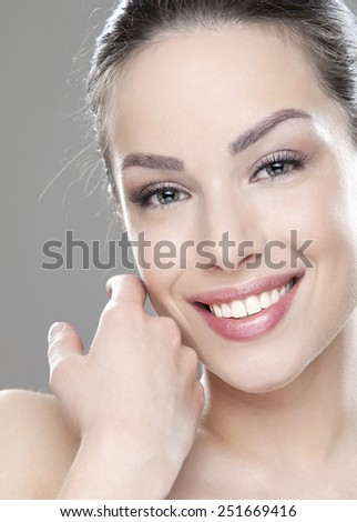 Close-up portrait of a beautiful young woman holding hands by her face and looking at camera - stock photo