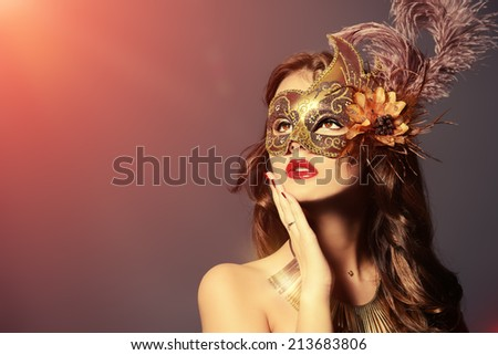 Close-up portrait of a beautiful young woman in a carnival mask. Vintage - stock photo