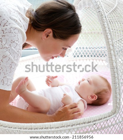 Close up portrait of a beautiful young woman looking at baby in bed - stock photo