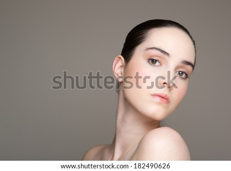 Close up portrait of a beautiful young woman on gray background - stock photo