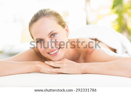 Close up portrait of a beautiful young woman on massage table over white background - stock photo