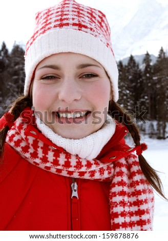 Close up portrait of a beautiful young woman on vacation in the snow mountains, smiling at the camera and wearing red winter clothing during a sunny cold day, outdoors.