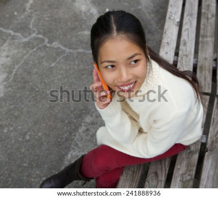Close up portrait of a beautiful young woman sitting on park bench and calling by mobile phone - stock photo
