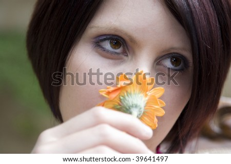 Close-up portrait of a beautiful young woman smelling a yellow flower. - stock photo