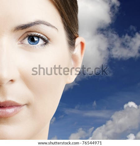 Close-up portrait of a beautiful young woman with  a cloudy sky on the background - stock photo