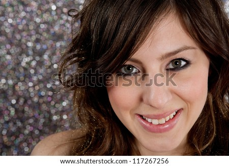 Close up portrait of a beautiful young woman with party make up on, smiling against a silver glitter background. - stock photo