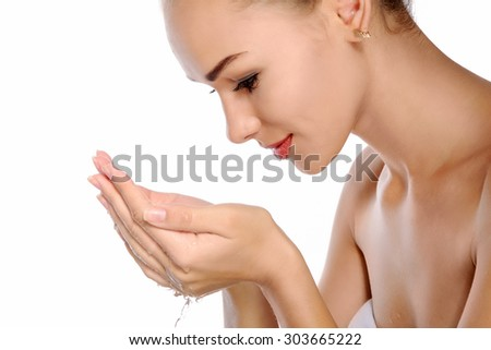 Close-up portrait of a beautiful young woman with perfect skin. She washes her face and clear water dripping from her hands. Side view against an isolated background - stock photo