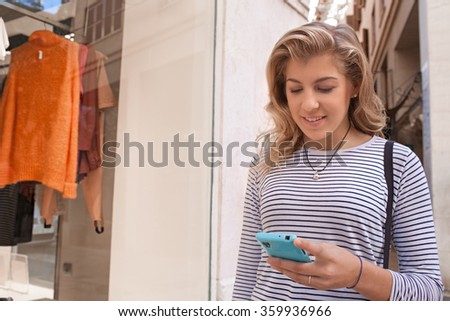 Close up portrait of a blond adolescent girl using a smartphone in city shopping street with store window, smiling and networking, outdoors. Teenager technology and consumer living, exterior.