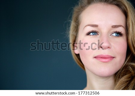 Close up portrait of a blond woman looking away - stock photo
