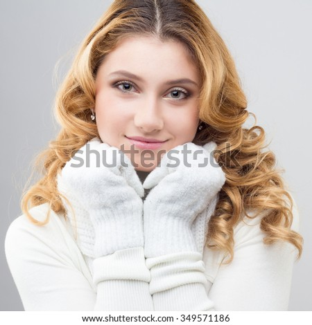 close-up portrait of a blonde girl in a warm white pullover isolated on white background - stock photo