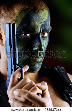 Close-up portrait of a brave soldier in war paint holding a gun. Black background. Military, war. Special forces. - stock photo