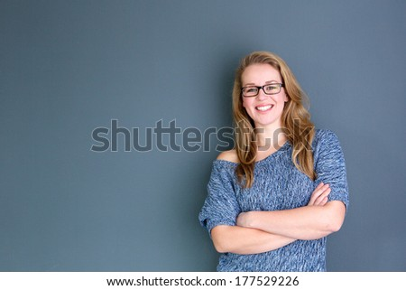 Close up portrait of a business woman standing against gray background with arms crossed - stock photo