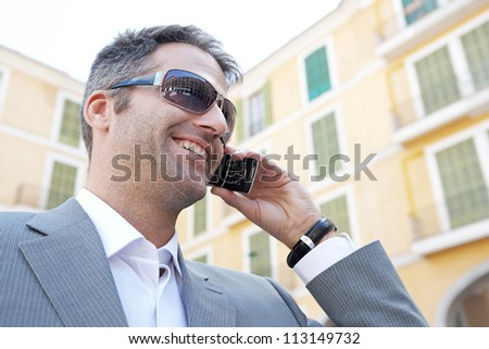 Close up portrait of a businessman having a phone conversation using his smart phone while standing in front of a classic building in the city, smiling. - stock photo