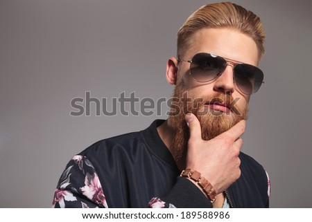 close up portrait of a casual young man holding his hand on his long red beard while looking into the camera. on gray studio background