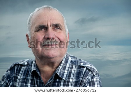 Close-up portrait of a Caucasian senior man with mustache against the background of the sea - stock photo
