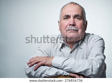 Close-up portrait of a Caucasian senior man with mustache wearing a white shirt while smiling at camera - stock photo