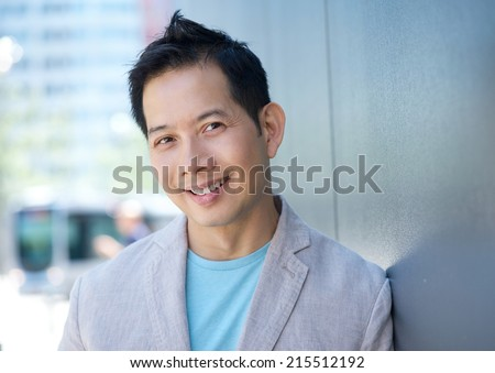 Close up portrait of a charming asian man smiling outdoors - stock photo