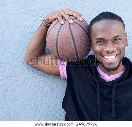 Close up portrait of a cheerful african american man holding basketball - stock photo