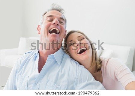 Close-up portrait of a cheerful couple in the living room at home - stock photo