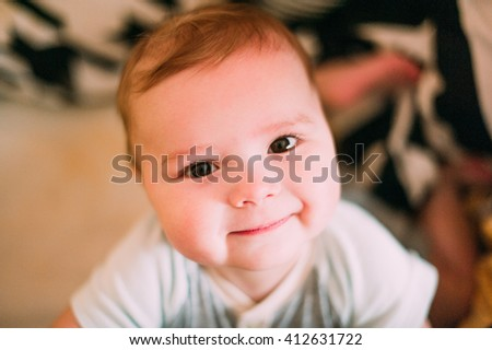 Close-up portrait of a cheerful cute baby in the crib at home - stock photo