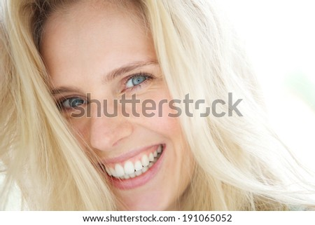 Close up portrait of a cheerful young blond woman smiling - stock photo