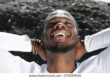 Close up portrait of a cheerful young man laughing outdoors with hands behind head - stock photo