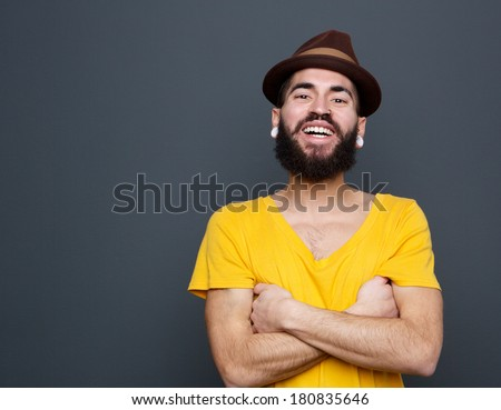 Close up portrait of a cheerful young man with beard laughing on gray background - stock photo